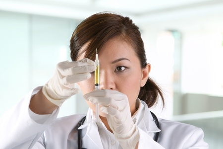 zastrzyk: Asian lekarz na sobie zielone zarośla i stetoskop trzymając strzykawkę.