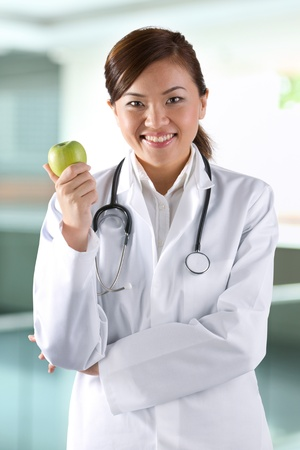Female Asian doctor holding an apple. Healthy eating concept. photo