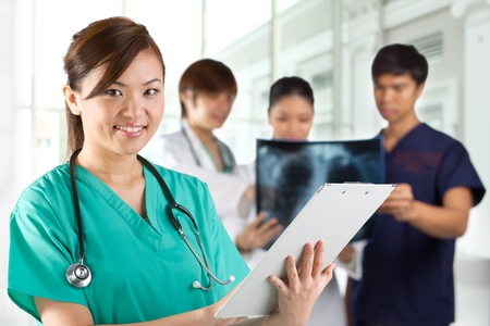 asian doctor: Asian Female doctor wearing a green scrubs and stethoscope. Her Colleges are out of focus in the background.
