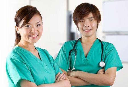 Asian doctors wearing a green scrubs and stethoscope.