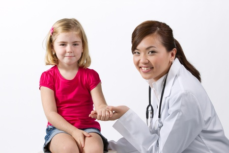 exam room: Asian Female doctor examining little girl with a stethoscope. Stock Photo