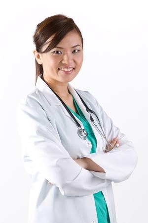 doctora: Mujer m�dico asi�tico que llevaba una bata blanca y estetoscopio. Aislado en blanco. Foto de archivo