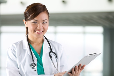 Female Asian doctor wearing a white coat and stethoscope. Stock Photo - 12245739