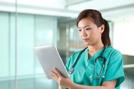 Female Asian doctor looking at a digital tablet & wearing a green scrubs plus stethoscope. photo