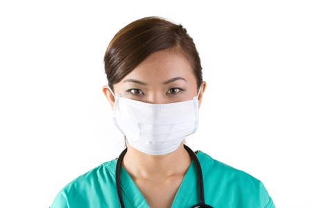 surgical light: Asian doctors wearing a face mask, green scrubs and stethoscope.