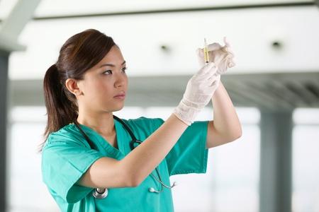 infirmi�re seringue: M�decin asiatique porte un gommage verts et le st�thoscope tenant une seringue.