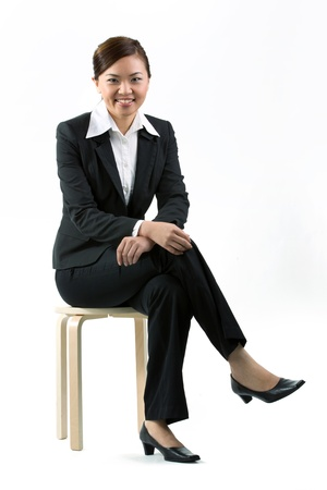 the stool: Asian business woman sitting on a stool. Isolated on white background.