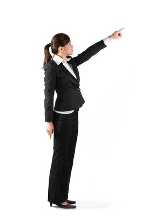 Full length portrait of a happy young Asian business woman pointing at something. Isolated on a white background photo