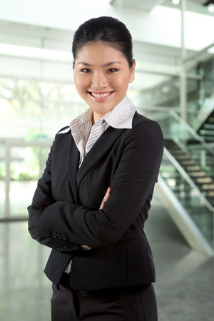 Portrait of a happy business woman standing with folded arms. photo