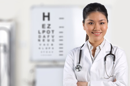 eye test: A female nurse with an eye test chart in the background. Stock Photo