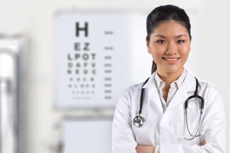 vision test: Una enfermera con una carta de examen de la vista en el fondo.