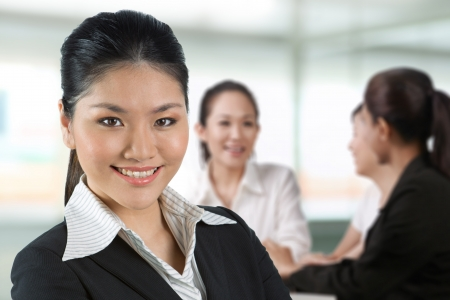 Asian business woman with her team in background. photo