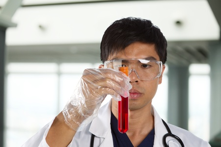 A male scientific researcher looking at a liquid solution. Stock Photo - 12595626