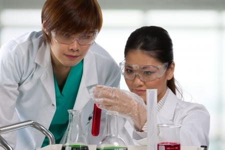 laboratorio clinico: Los investigadores cient�ficos buscando una soluci�n l�quida. Foto de archivo