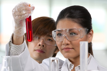 Scientific researchers looking at a liquid solution. photo