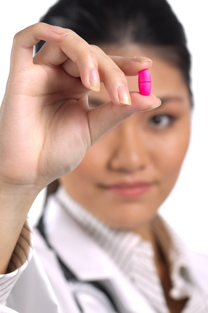 Portrait of an Asian female doctor holding up a pill. photo