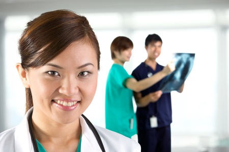 asian doctor: Female doctor with colleague in the background out of focus.
