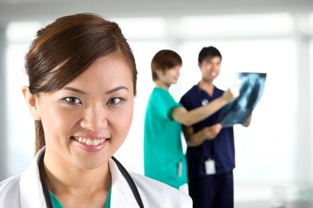 doctora: Mujeres m�dico con su colega en el fondo fuera de foco.
