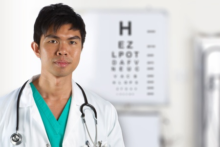 asian nurse: A male doctor with an eye test chart in the background.