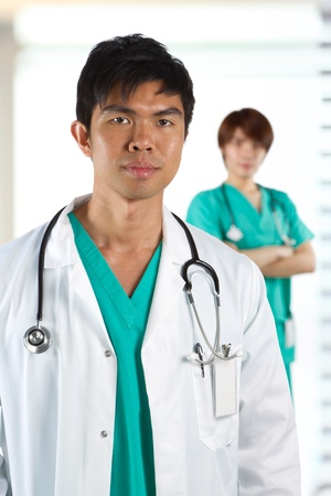 Closeup Portrait of a male doctor with colleague in background out-of-focus Stock Photo - 12596450