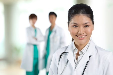 Female doctor with colleague in the background out of focus. Stock Photo - 12596453