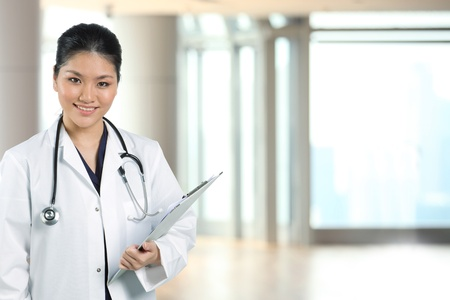 Female Asian doctor wearing a white coat and stethoscope. photo