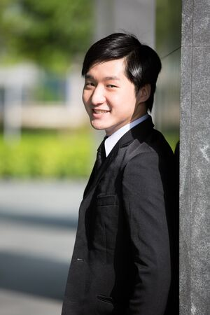 A young Asian business executive leaning against a wall. photo