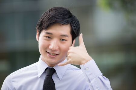 chinese adult: Portrait of an Asian businessman showing the call me symbol with his hands.