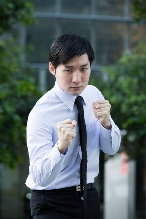 Asian Business man throwing a punch. Conceptual image. photo