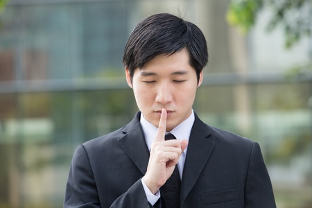 hushed: Asian Business man with his finger on his lips asking for silence.