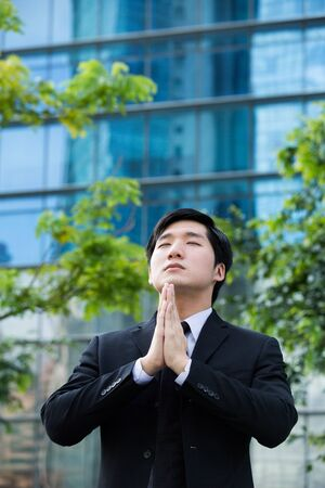 Coneptual image of an Asian Businessman praying for success  photo