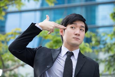 Conceptual portrait of a desperate Asian business man. photo