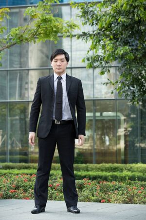 Young Asian business man standing outside an office building. photo