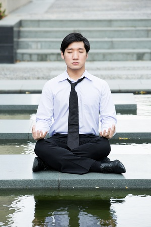 Asian business man meditating in work shirt and tie. photo