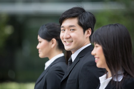 Group of happy Asian business people standing in row. photo