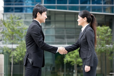 Asian business man and woman shaking hands. Stock Photo - 13194287