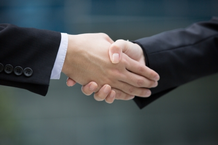 men shaking hands: Closeup hand shake between two business man and woman.