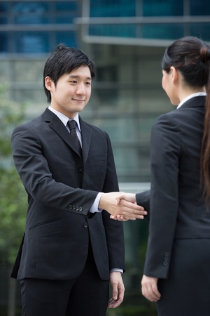 Asian business man and woman shaking hands. Stock Photo - 13194375