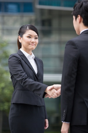Asian business man and woman shaking hands. photo