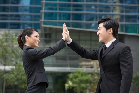 doing business: Happy Asian business people doing a high five.
