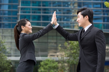five people: Happy Asian business people doing a high five.