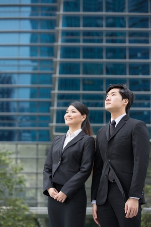 Asian business people standing in front of a skyscraper. photo