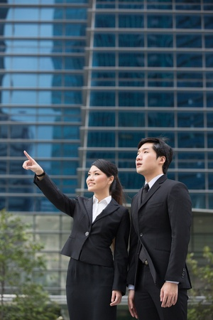 Two Asian business people pointing and looking at something. photo