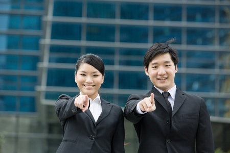 Asian business man and woman pointing at the viewer.  photo