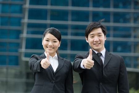 Asian businessman and businesswoman with thumbs up outside office. Stock Photo - 13236204