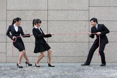 against the war: Two Asian businesswomen playing tug of war against one businessman. Stock Photo