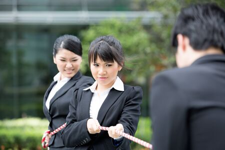 Asian businesswomen playing tug of war against one businessman. photo