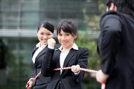 unfair: Asian businesswomen playing tug of war against one businessman. Stock Photo