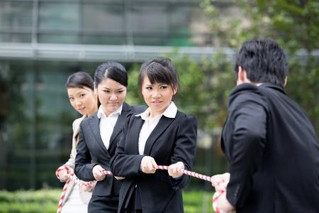 disadvantage: Asian businesswomen playing tug of war against one businessman. Stock Photo