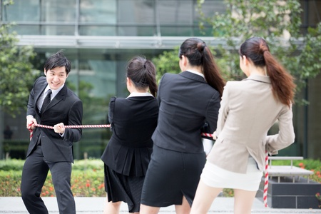 Asian businesswomen playing tug of war against one businessman. Stock Photo